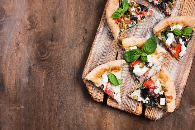 Tranches De Pizza Sur Une Planche à Découper à Plat Photo gratuit