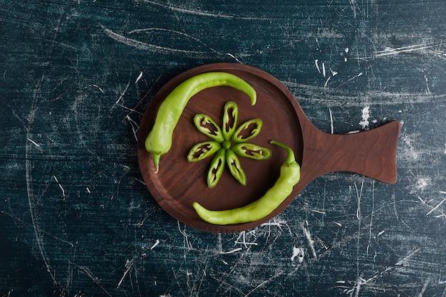 Tranches De Poivron Vert En Forme De Fleur Sur Planche De Bois. Photo gratuit