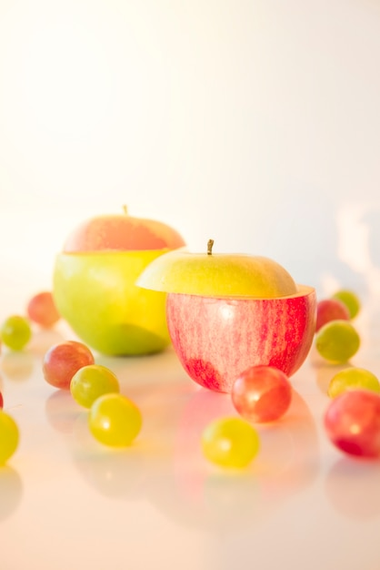 Tranches de pomme rouge et verte avec des raisins sur fond blanc Photo gratuit