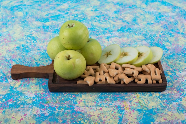 Tranches De Pommes Vertes Avec Des Craquelins Sur La Planche De Bois, Au Centre. Photo gratuit