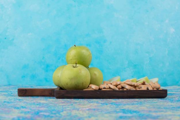Tranches De Pommes Vertes Avec Des Craquelins Sur La Planche De Bois Sur Bleu. Photo gratuit