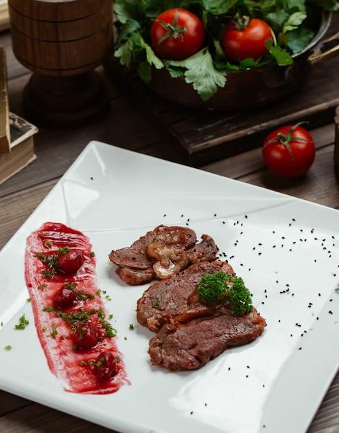 Tranches de steak d'agneau avec cerise de cornaline et sauce sur une assiette carrée blanche Photo gratuit