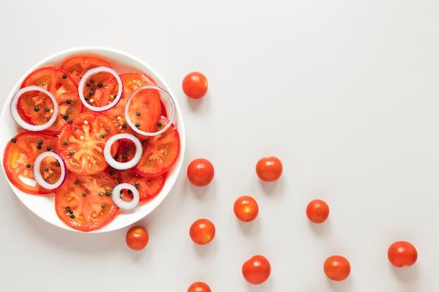 Tranches de tomates et d'oignons dans une assiette sur fond blanc Photo gratuit