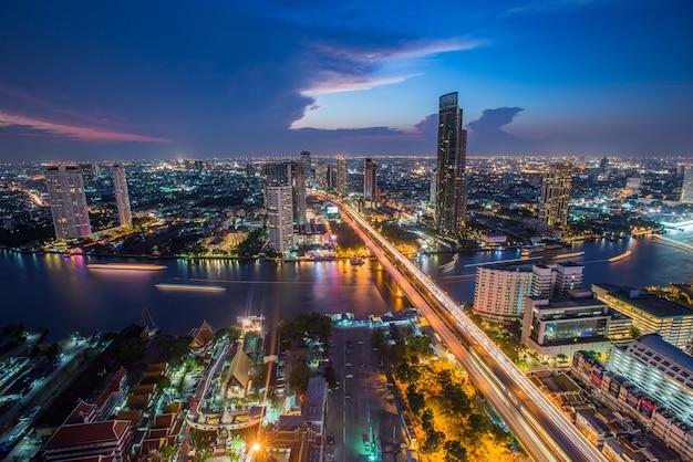 Transport de bangkok au crépuscule avec le bâtiment d'affaires moderne le long de la rivière (thaïlande) - panorama Photo Premium