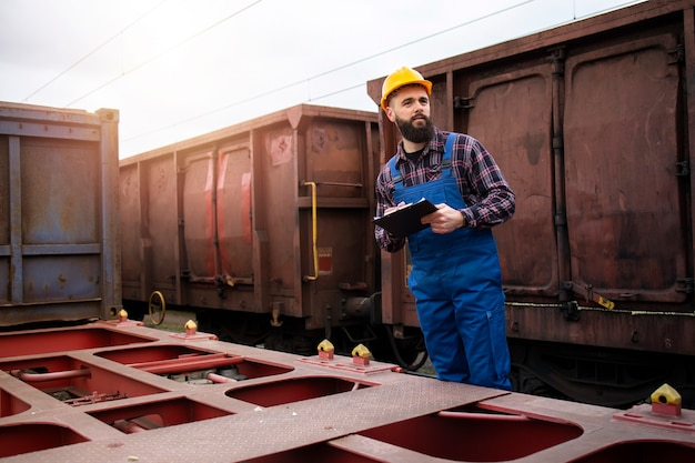 Transporteur De Chemin De Fer Avec Presse-papiers Pour Garder Une Trace Des Conteneurs De Fret Prêts à Quitter La Gare Photo gratuit