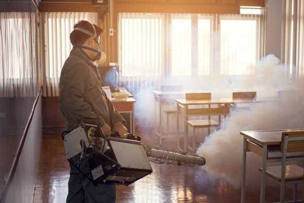Travail de brumisation visant à éliminer les moustiques pour prévenir la propagation de la dengue et du virus zika Photo Premium