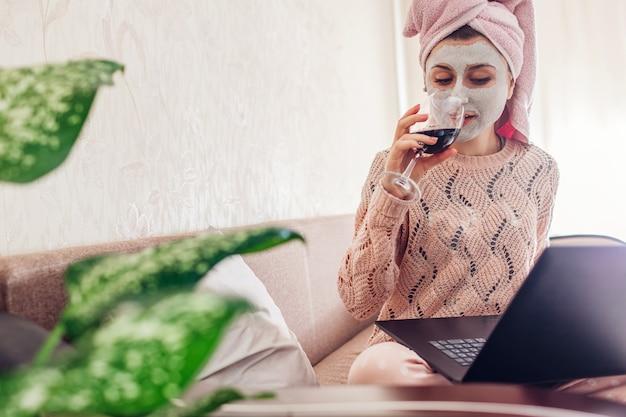 Travail à Domicile Pendant La Quarantaine Des Coronavirus. Femme Avec Masque Facial Appliqué à Boire Du Vin à L'aide D'un Ordinateur Portable Sur Le Verrouillage Photo Premium