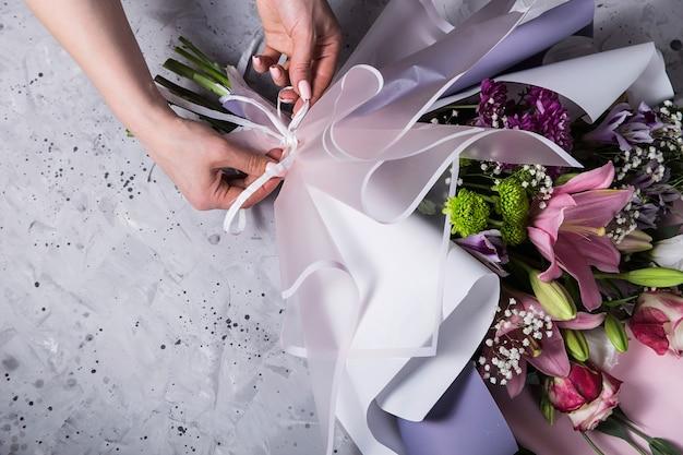 Travail de fleuriste en train de créer un bouquet de lis sur le lieu de travail Photo Premium
