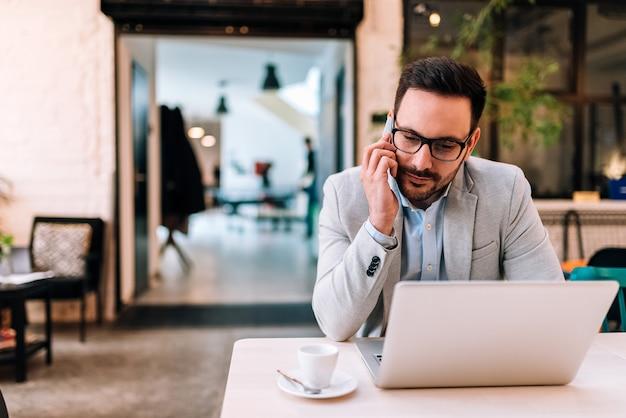 Travailler avec plaisir jeune homme parlant au téléphone mobile et regardant son ordinateur portable assis au café. Photo Premium