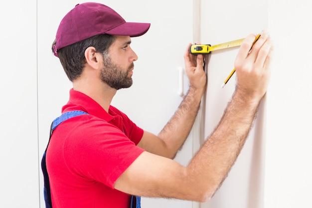 Travailleur de la construction à l'aide d'un ruban à mesurer Photo Premium