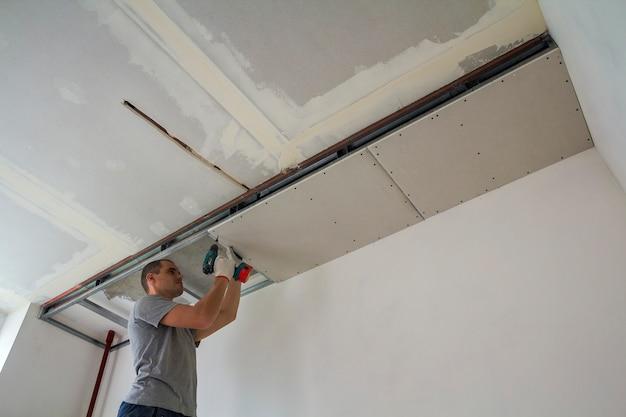 Travailleur De La Construction Assembler Un Plafond Suspendu Avec Des Cloisons Sèches Et Fixer La Cloison Sèche Au Cadre Métallique Du Plafond Avec Un Tournevis. Photo Premium