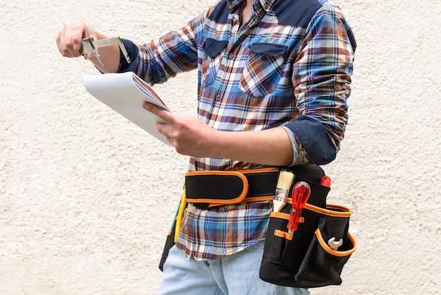 Travailleur De La Construction Dans Une Chemise à Carreaux Bleue Avec Des Outils Dans Sa Ceinture. Photo Premium