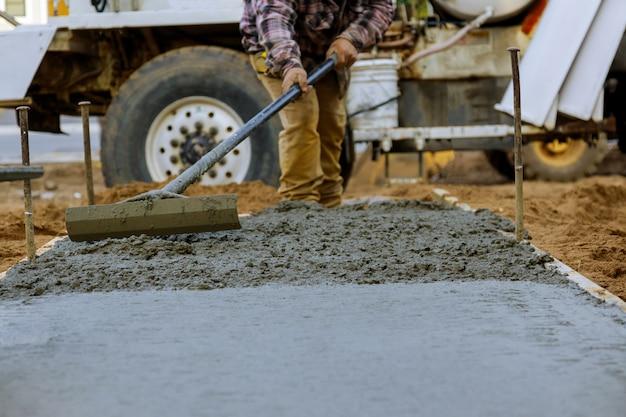 Travailleur De La Construction Pour Ciment Pour Trottoir Dans Les Travaux De Béton Avec Camion Malaxeur Avec Brouette Photo Premium