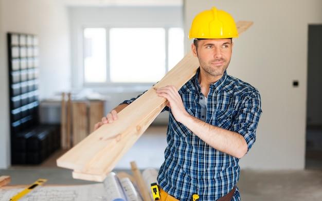 Travailleur De La Construction Tenant Des Planches De Bois Photo gratuit