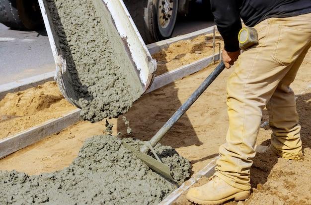 Travailleur De La Construction Verser Le Ciment Pour Trottoir Dans Les Travaux De Béton Avec Camion Malaxeur Avec Brouette Photo Premium