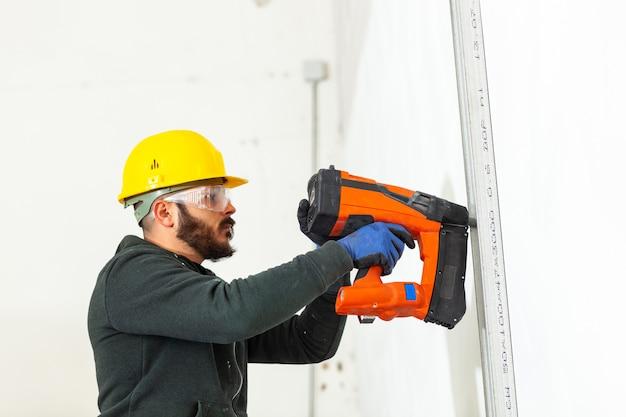 Travailleur construit un mur de plaques de plâtre. Photo Premium