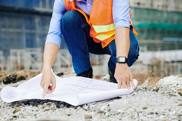 Travailleur De Costruction Pointant Sur Plan De Construction Photo Premium