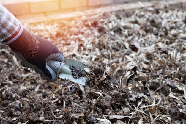 Travailleur creuse le sol noir avec une pelle dans le potager, à l'extérieur Photo Premium