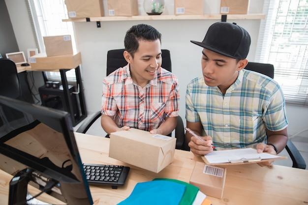 Travailleur Du Commerce électronique. Homme Avec Partenaire Et Produit Photo Premium