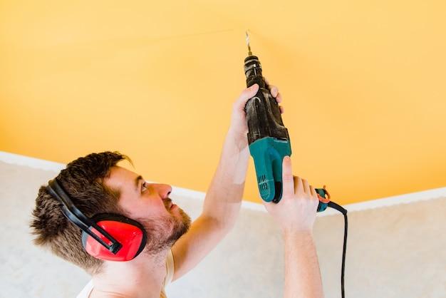Travailleur fait des réparations et des exercices dans le plafond Photo Premium