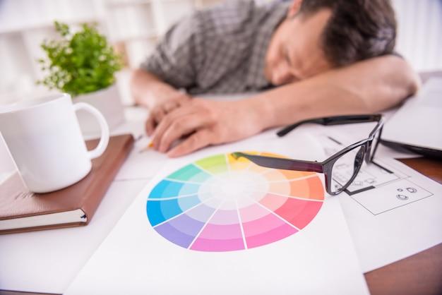 Travailleur fatigué, dormant sur le lieu de travail plein de croquis Photo Premium