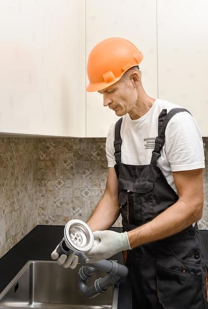 Le Travailleur Installe Un Drain D'égout Pour L'évier De La Cuisine. Photo Premium