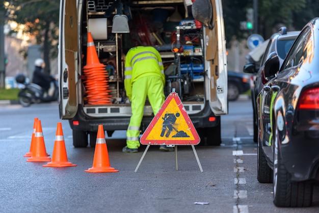 Travailleur à l'intérieur de sa camionnette, chargé d'outils, protégé du trafic par des cônes Photo Premium