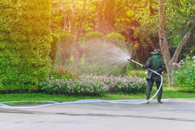 Travailleur jardinier pulvériser arbre et plante dans le parc chaque matin Photo Premium