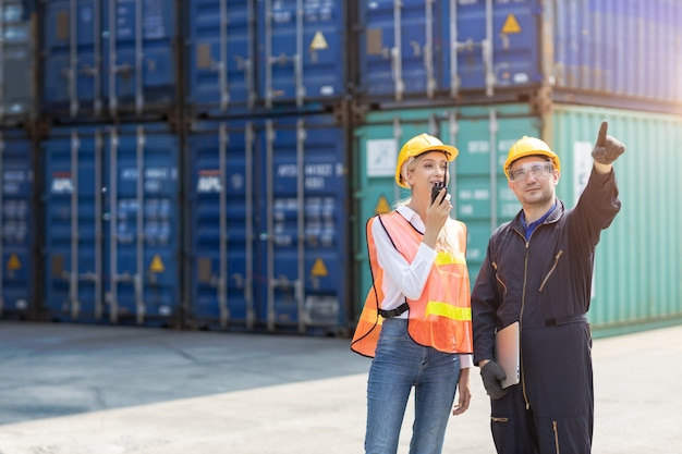 Travailleur Logistique Homme Et Femme équipe De Travail Avec Contrôle Radio Des Conteneurs De Chargement Au Port De Fret Aux Camions Pour L'exportation Et L'importation De Marchandises. Photo Premium