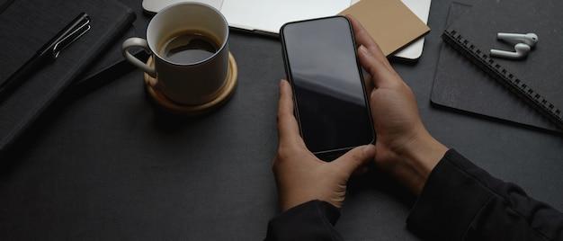 Travailleur Masculin Mains Tenant Le Smartphone Sur Le Bureau De Bureau Moderne Sombre Photo Premium