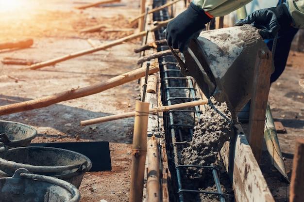 Travailleur mélangeant pour ciment de construction sur le sol pour la maison de construction Photo Premium