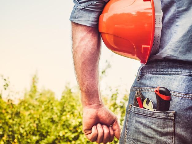 Travailleur avec des outils et un casque orange Photo Premium