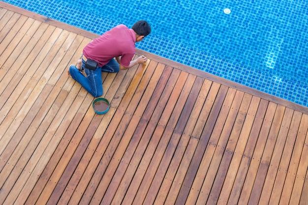 Un Travailleur Peinture Terrasse En Bois Piscine Extérieure