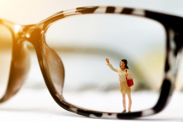 Travailleur de personnes miniature, nettoyage des lunettes. Photo Premium