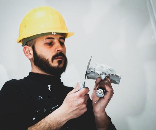 Travailleur plâtrant mur en plaques de plâtre. Photo Premium
