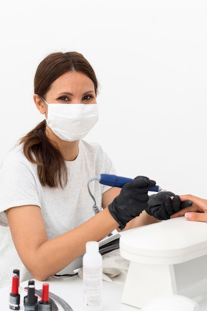 Travailleur Portant Un Masque Au Salon De Manucure Photo gratuit