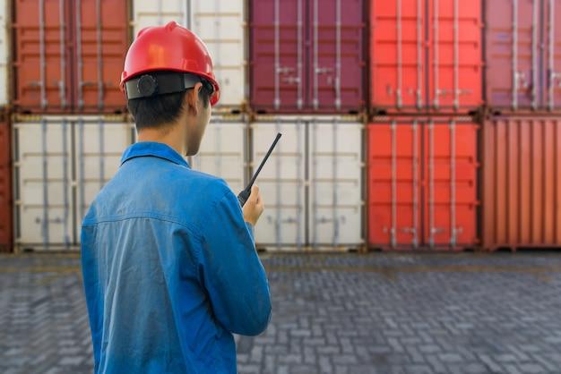 Travailleur De Quai Parlant Au Talkie-walkie Pour Contrôler Le Chargement Des Conteneurs Dans Un Port Industriel Photo Premium