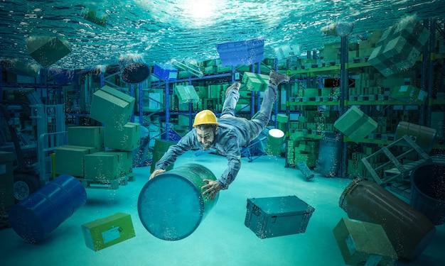 Un travailleur s'accroche à une poubelle dans un entrepôt totalement inondé. Photo Premium