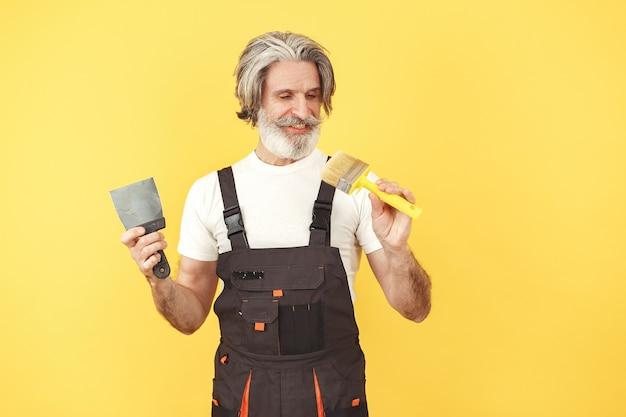 Travailleur En Salopette. Homme Avec Des Outils. Senior Avec Spatule. Photo gratuit