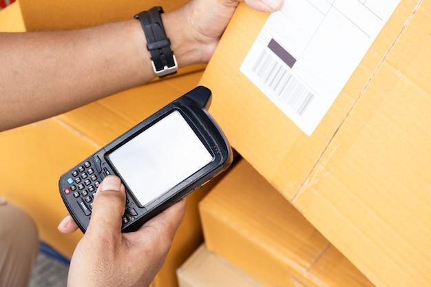 Un travailleur tient un lecteur de code à barres avec balayage sur les produits Photo Premium