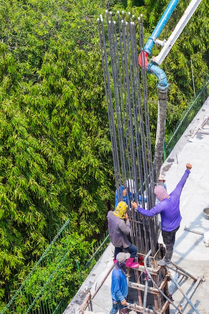 Travailleur en train de verser du ciment dans les fondations et le coffrage de piliers sur un chantier de construction. Photo Premium