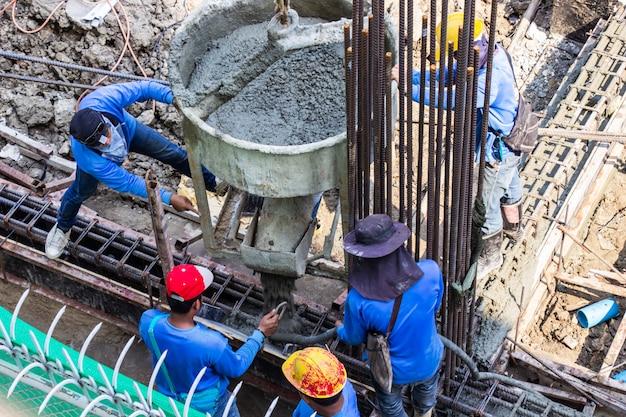 Travailleur en train de verser du ciment dans les fondations du coffrage sur le chantier. Photo Premium