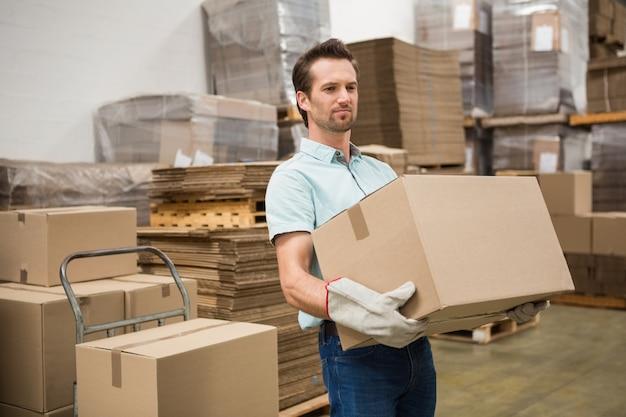 Travailleur transportant une boîte dans un entrepôt Photo Premium