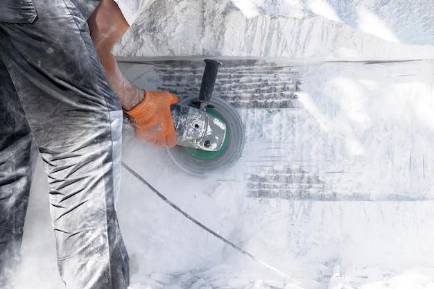 Le travailleur travaille comme une meule sur une pierre blanche. Photo Premium