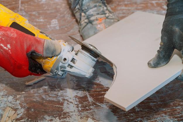 Travailleur utilisant un outil de broyage pour couper des carreaux avec de la poussière en arrière-plan. Photo Premium