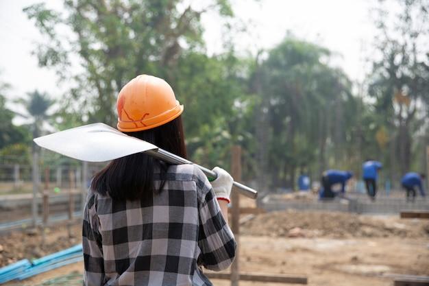 Travailleurs de la construction portant une pelle sur le chantier Photo gratuit