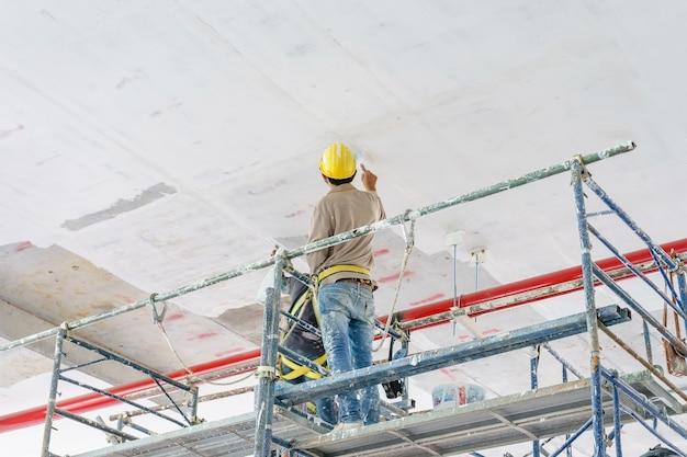 Travailleurs de la construction de la tour d'échafaudage peinture et rénovation de plancher du bâtiment Photo Premium
