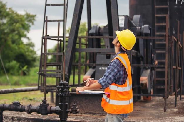 Les travailleurs debout et vérifiant à côté des pompes à huile de travail. Photo gratuit