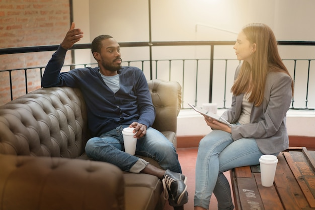 Travailleurs discutant avec désinvolture des idées sur un canapé dans le lieu de travail moderne Photo Premium