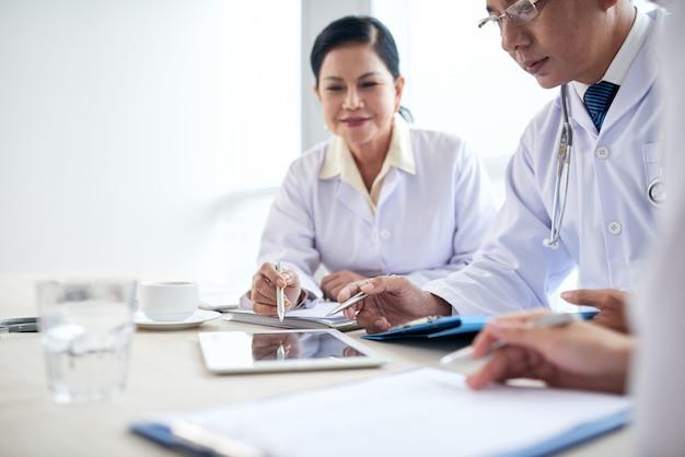 Les travailleurs de l'hôpital analysant des données médicales lors d'une réunion Photo gratuit